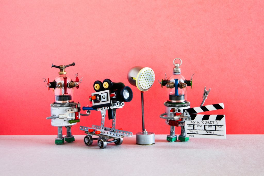 Funny robot cameraman and clapperboard assistant
